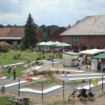 Blick auf den Minigolfplatz während des Kunsthandwerkermarktes (rechts auf Kundenparkplatz). Im Hintergrund Außenterrasse des Bauerncafes. Wiese mit Tieren beginnt links hinter dem Spielplatz.